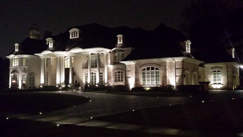 large home's facade lit by floodlights