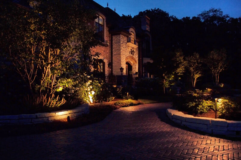 large house and brick driveway illuminated in evening