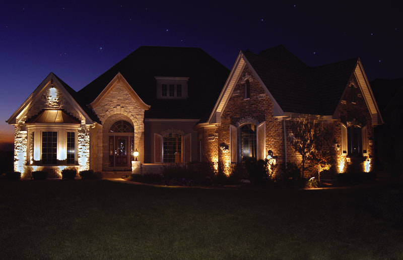 large home facade lit up in evening by front lights