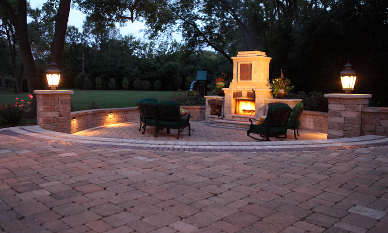 large brick patio with fireplace and chimney at night