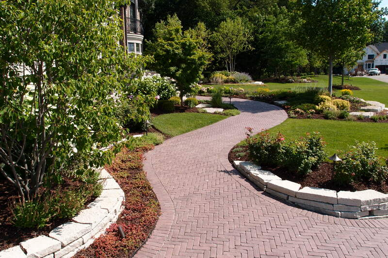 winding brick walkway surrounded by plant life and yard