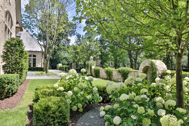 manicured lawn with a garden and stone wall covered in foliage