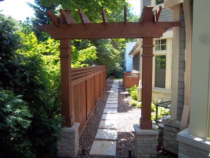 long walkway along side of a house with a fence and foliage