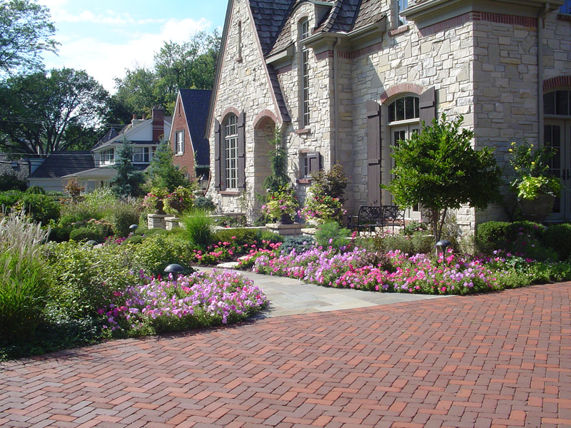 stone pathway to front entrance of mansion surrounded by colorful garden