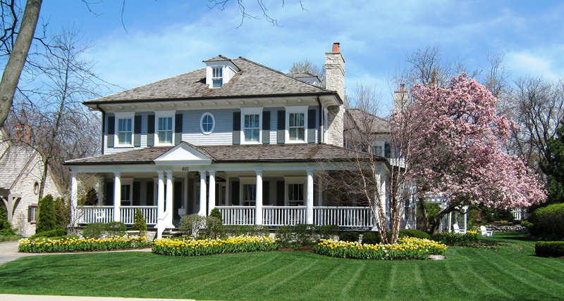 wide shot of large home with maintained lawn and colorful garden in front
